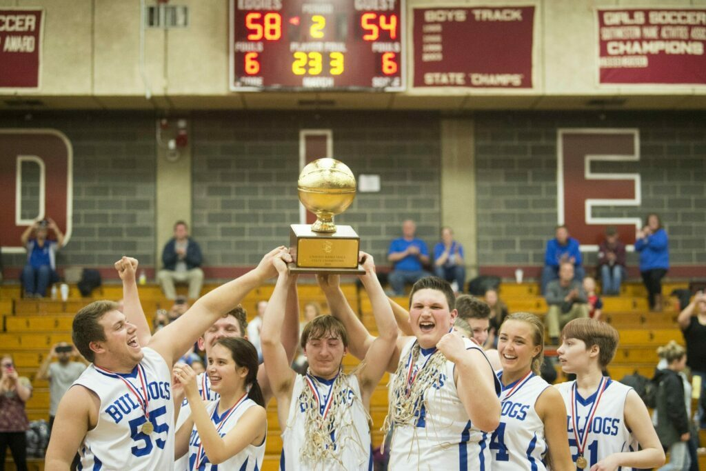 Madison Area Memorial High School's Scott Sawtelle (1) hoists the gold ball over his head with his teammates after defeating Westbrook High School in the Unified Championship game at Edward Little High School in Auburn on Tuesday.