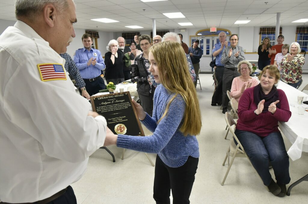 China Village Fire Chief Tim Theriault presents a lifesaving award plaque to Aislynn Savage, 12, on Tuesday during the annual Fire Department meeting in China. Aislynn's mother Laura, right, and firefighters and family applaud. Aislynn was recognized for her actions on Feb. 23 when her mother experienced a medical incident while driving. Aislynn took the wheel and guided the car safely into a snowbank and avoided hitting trees or vehicles.