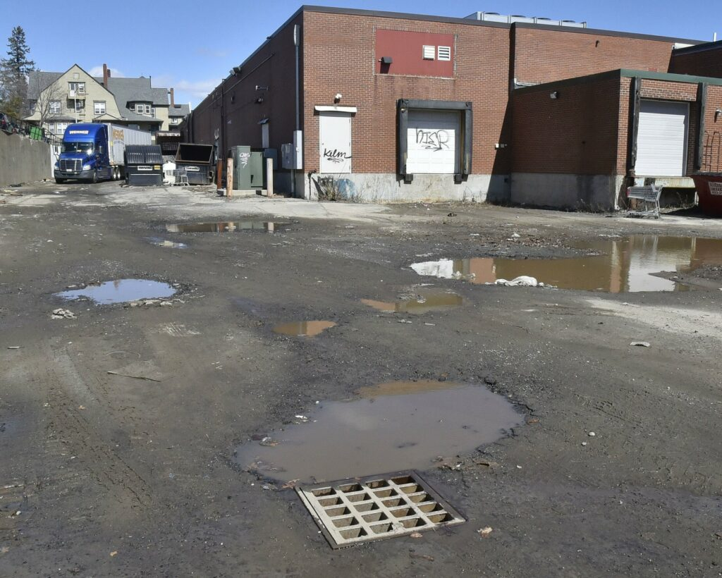 A delivery truck passes through a nearly dry parking lot behind stores in The Concourse in Waterville on Monday. The lot was flooded with several feet of muddy water from a broken water main on Sunday. Firefighters used a boat and an officer in the water to locate the drain, foreground, before unplugging it to free the water.
