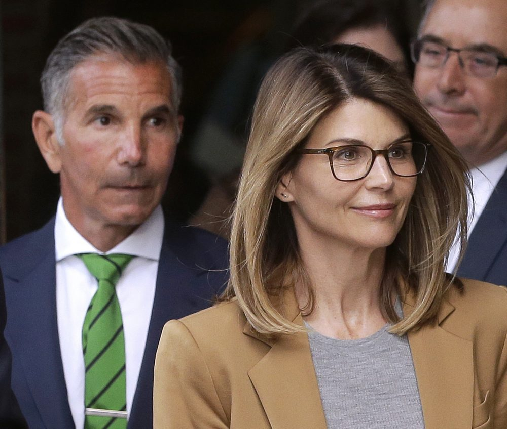 Actress Lori Loughlin, front, and husband, clothing designer Mossimo Giannulli, depart federal court in Boston on Wednesday.