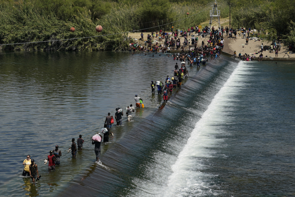 Haitian migrants use a dam Sept. 18 to cross into the United States from Mexico in Del Rio, Texas.