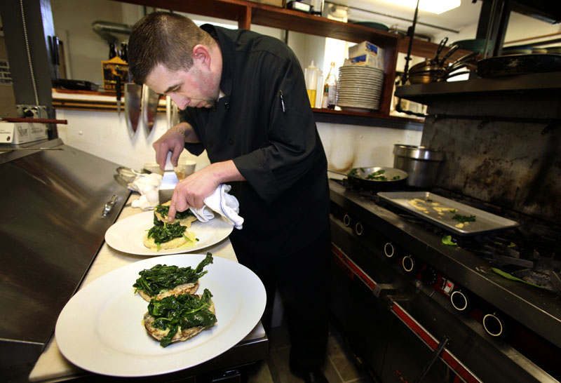 "Paul Dyer, executive chef at the Porthole, prepares eggs Florentine, which is ""probably our number one-selling dish right now on our menu,"" he said."