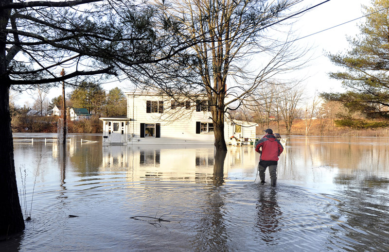 Michael Senechal of Westbrook walks through floodwaters to return to his house at 40 Lincoln St. on Friday. He said he plans to move, this being his third experience with the Presumpscot River overflowing its banks.