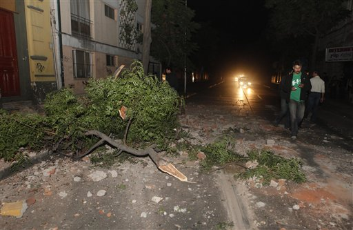 Residents walk by debris and a broken branch outside their house in Santiago.