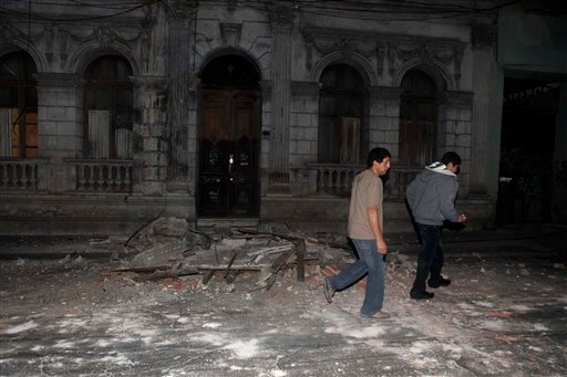 Residents walk by debris in Santiago, Chile's capital, after an earthquake struck. The quake hit 200 miles (325 kilometers) southwest of the capital, and the epicenter was just 70 miles (115 kilometers) from Concepcion, Chile's second-largest city,