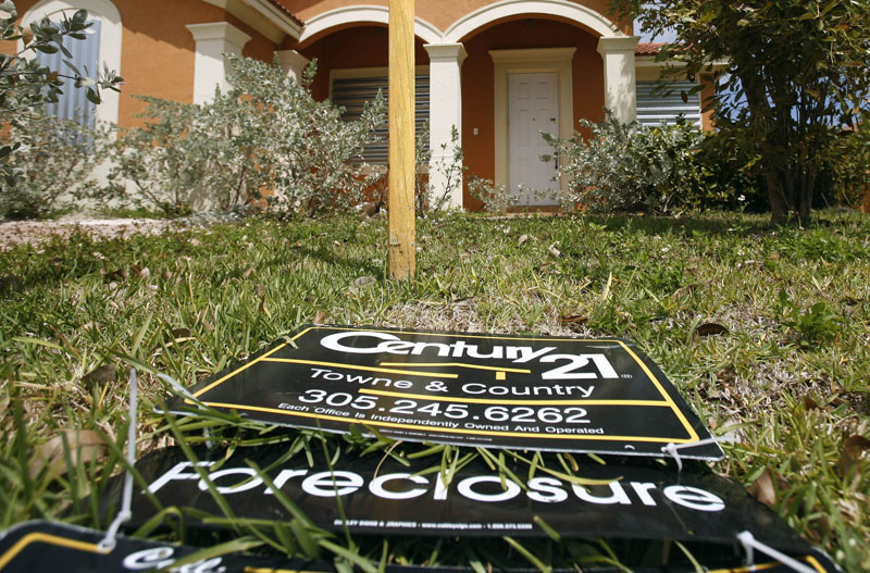 A sign lies on the ground in front of a foreclosed home in Homestead, Fla. The number of borrowers falling behind on their mortgage payments dropped sharply at the end of 2009, a sign the foreclosure crisis is beginning to ebb.