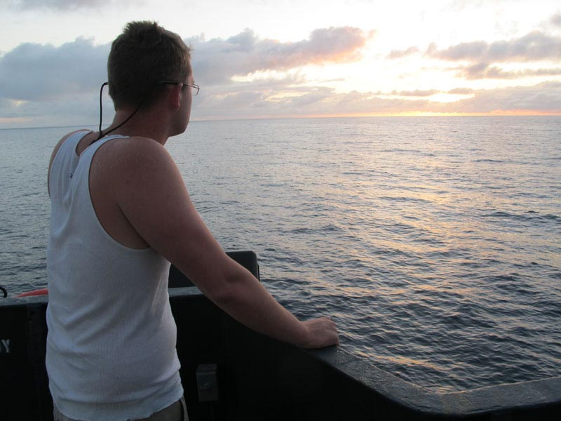Deckhand Nick Snyer of Hopkinton, Mass., watches the sunrise as the Sea Hunter sails for Haiti this morning.