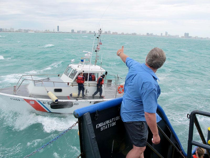 Sea Hunter owner Greg Brooks, cleared to continue his humanitarian mission to Haiti, waves farewell to Coast Guard inspectors this morning.