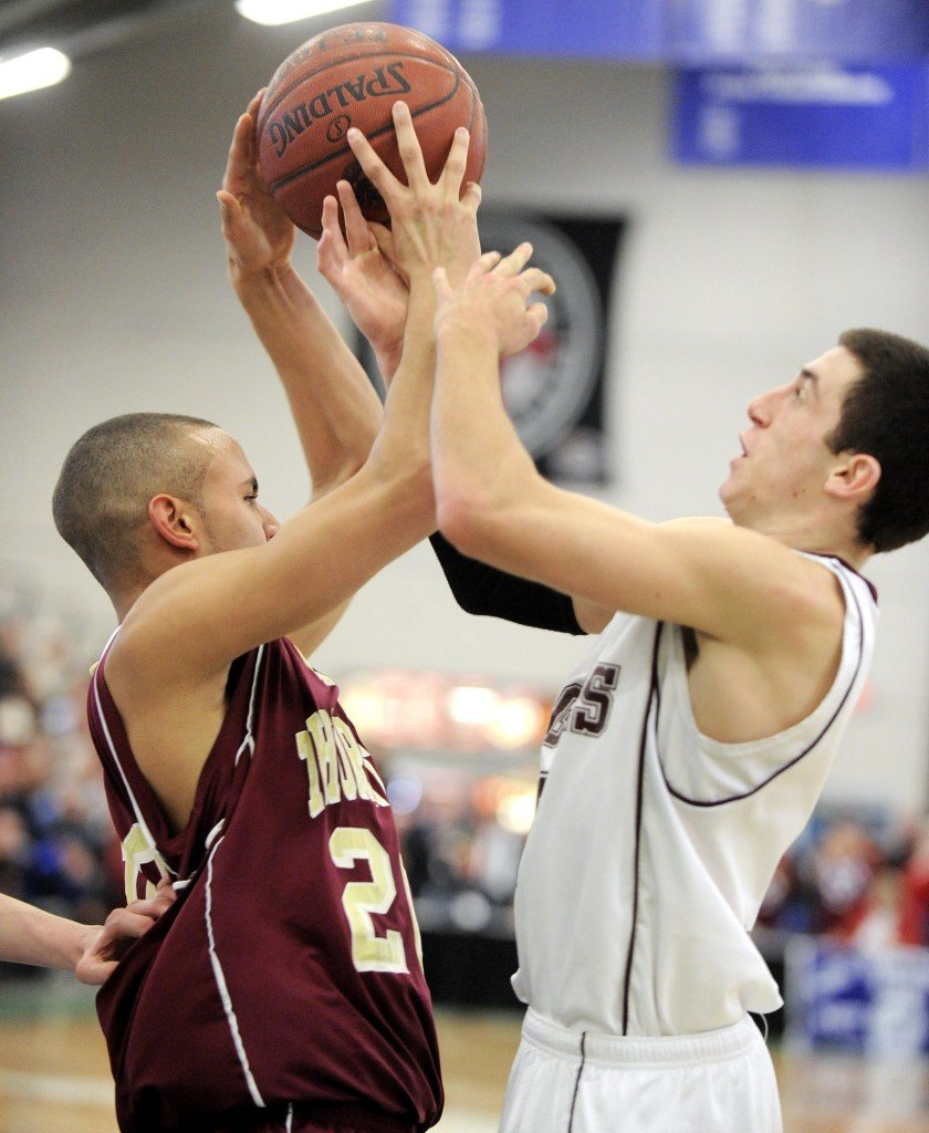 Tyler Tholl of Thornton Academy, left, and Adam Szklany of Windham compete for a rebound Friday night during their Western Class A quarterfinal at the Portland Expo. Windham earned a 59-42 victory.