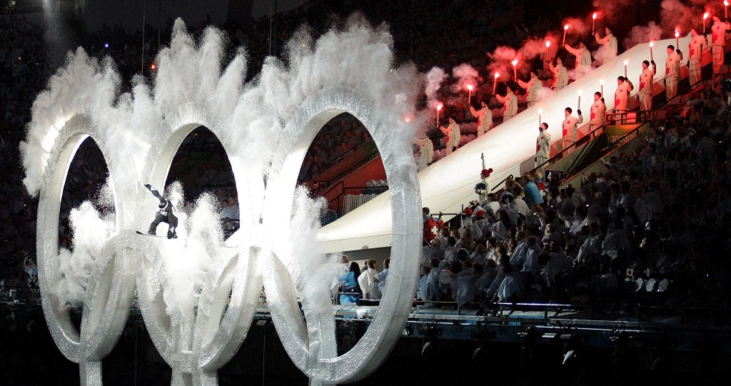 A snowboarder jumps through the Olympic rings during the opening ceremony for the Vancouver 2010 Olympics in Vancouver, British Columbia, Friday, Feb. 12, 2010.(AP Photo/David J. Phillip)