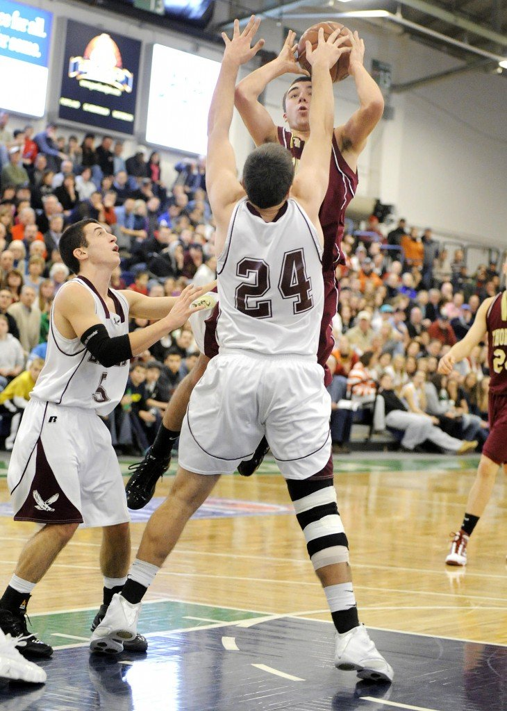 Photo by John Ewing/Staff Photographer... Friday, February 12, 2010...Windham vs. Thornton Academy boys basketball tournament game at the Expo. Windham's #24, Nick Taylor, blocks a jumpshot by Thornton's Corbett Smith.