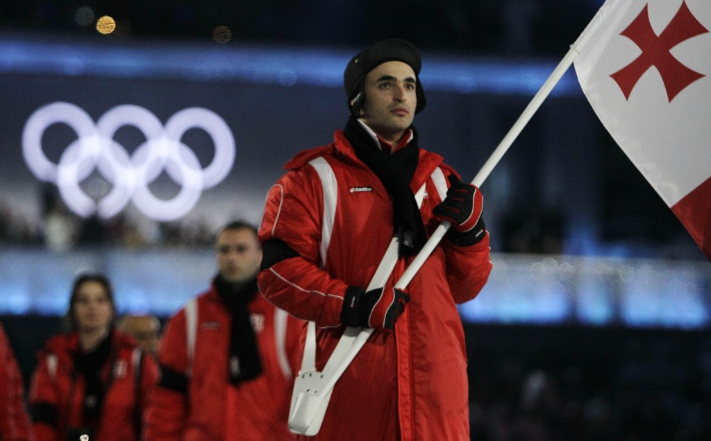 Georgia's Iason Abramashvili carries his nation's flag during the opening ceremonies Friday for the 2010 Winter Olympics in Vancouver. He wears a black armband in memory of countryman Nodar Kumaritashvili, who died during luge training earlier in the day.