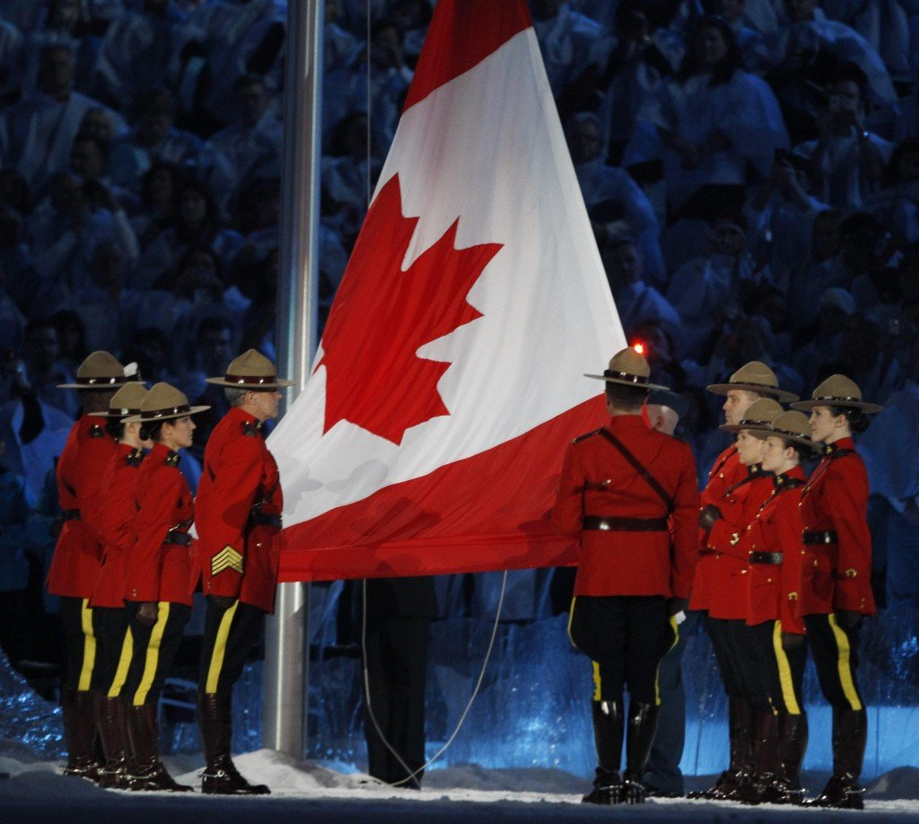 The Canadian flag is raised by members of the Royal Canadian Mounted Police during opening ceremonies for the Winter Olympics on Friday.
