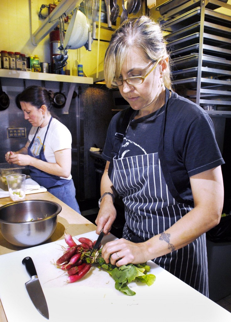 Krista Kern Desjarlais, chef and owner of Bresca in Portland, prepares French breakfast radishes Thursday for a starter served with olive oil and goat butter. At left is sous chef Courtney Loreg. Inset photo shows shrimp on the barby at Hugo's.