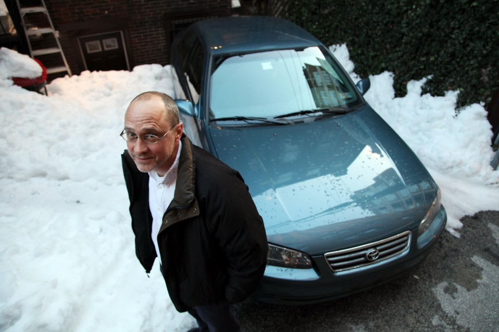 John Caskey stands with his 2001 Toyota Camry in Philadelphia. Caskey is an economics professor at Swarthmore who recently bought the Camry and sees absolutely zero sense in buying a new car.