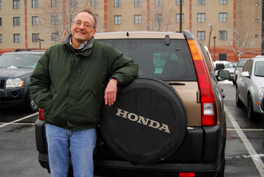 "Bill Stull leans against his Honda CR-V at Temple University in Philadelphia, where he is the chairman of the economics department. ""A car is a presentation of self,"" Stull said. ""I am sort of a practical person who ís not particularly interested in showing anything other than practicality in the kind of car I buy."""