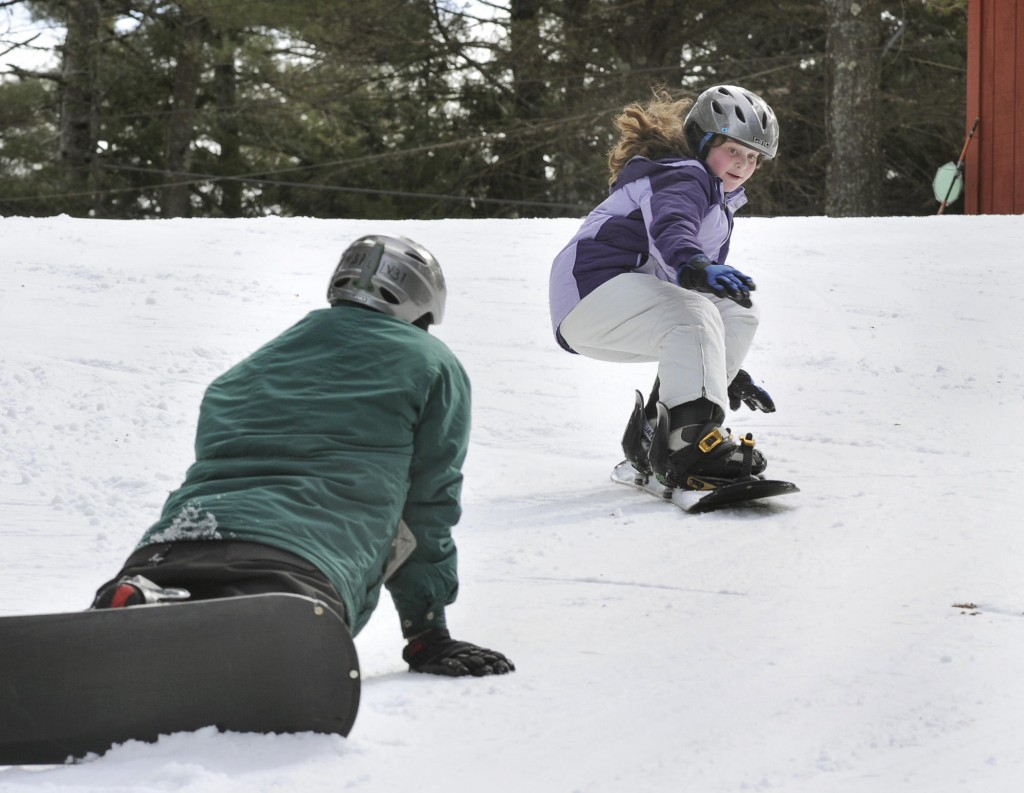 Deidre, 11, snowboards past dad Drew.