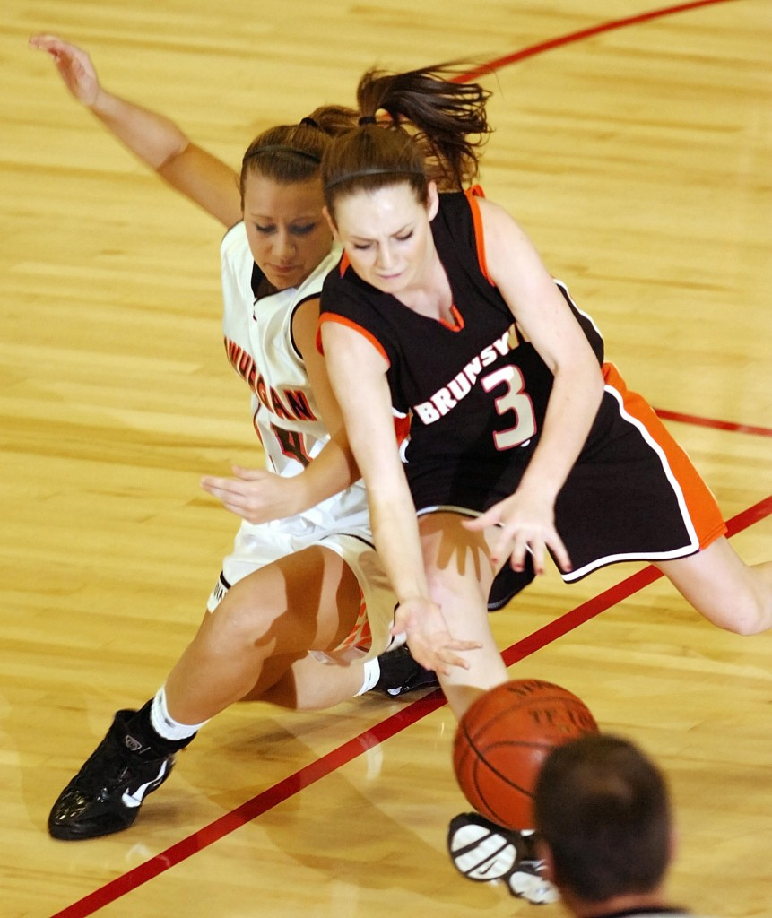 Staff photo by Joe Phelan Skowhegan sophomore guard Amanda Johnson, left, and Brunswick senior guard Hilary Champagne chase a loose ball during the Eastern Maine Class A regional girls basketball championship Friday at the Augusta Civic Center. Skowhegan won 38-36.