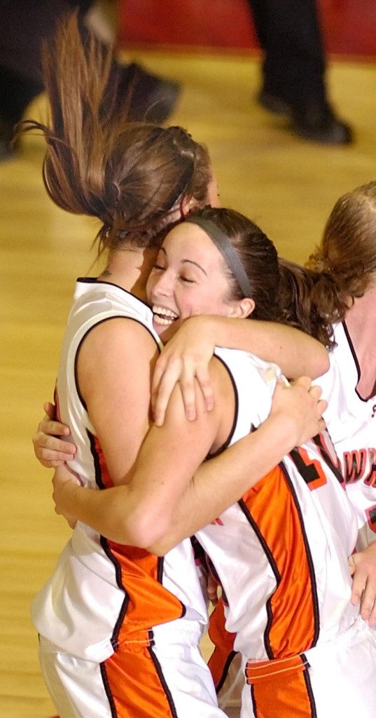 Staff photo by Joe Phelan Skowhegan senior forward Mackenzie Smith, left, hugs senior guard Liz Noddin right after Noddin sank a last second shot to win the Eastern Maine Class A regional girls basketball championship Friday at the Augusta Civic Center over Brunswick by a score 38-36.