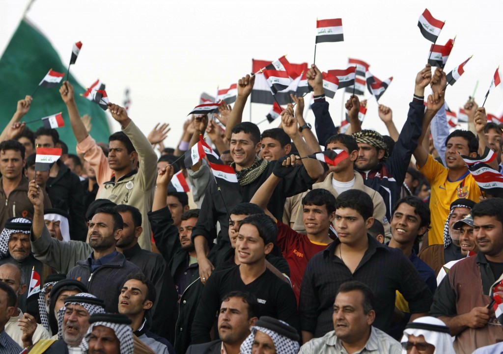 Men wave the Iraqi flag at a campaign rally attended by Prime Minister Nouri al-Maliki in Basra, Iraq, on Saturday.