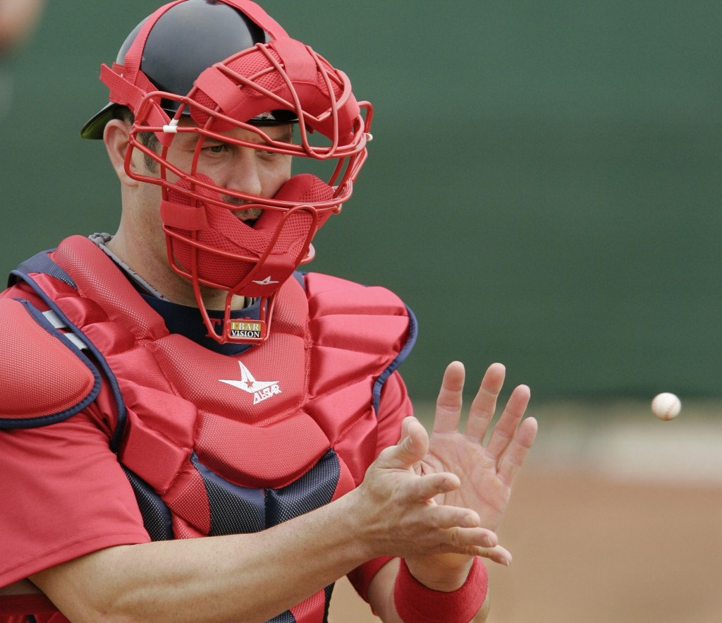 Jason Varitek catches a miniature baseball during the first day of spring training for pitchers and catchers on Saturday at Fort Myers, Fla. It's a different camp for the Boston veteran, now a backup to Victor Martinez.
