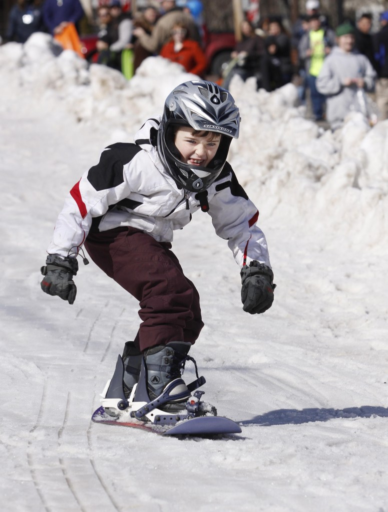 Camden Kelly, 7, of Saco snowboards on the sliding hill built on Old Orchard Street with trucked-in snow.