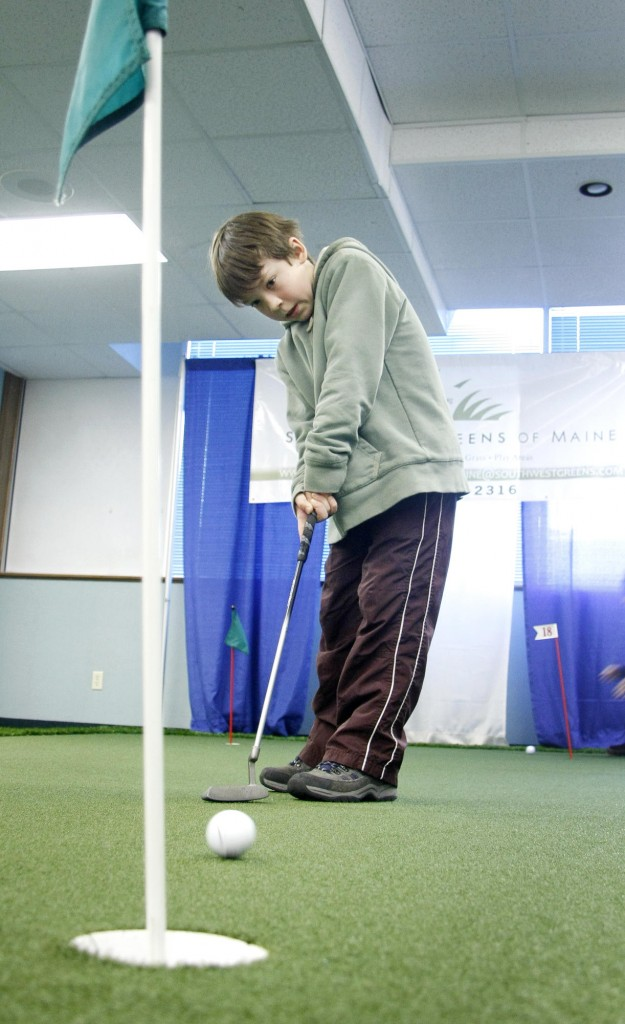 "Isaiah Anderson, 10, of South Portland practices his putting as part of ""adjusting his accuracy"" during the golf expo at the Holiday Inn by the Bay in Portland. ""I can't make the close shots so much,"" the fifth-grader said."