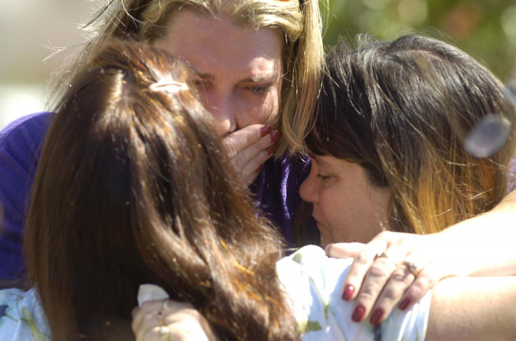 Donna Powell, from left, Brandie Geary and Michele Zorbis, all of Palm Bay, console each other.