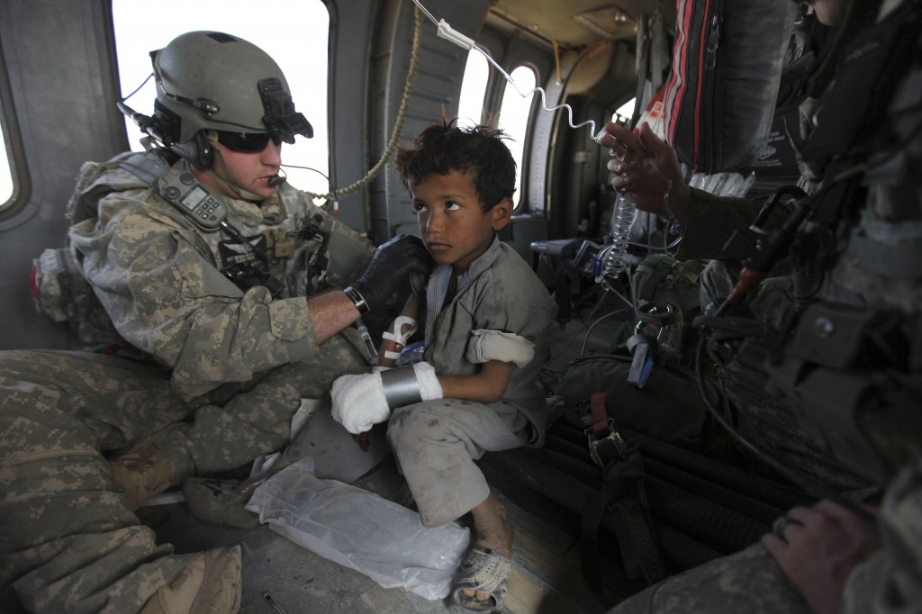 Airborne over Marjah, U.S. Army flight medic Sgt. Bryan Eickelberg of Arden Hills, Minn., tends to an Afghan boy wounded earlier by an improvised explosive device, according to troops on the ground on Tuesday in Afghanistan.