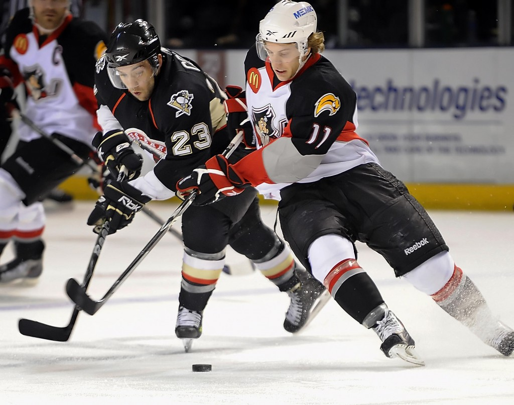 Tyler Ennis, right, of the Portland Pirates attempts to control the puck against Chris Connor of the Wilkes-Barre/Scranton Penguins in Portland's 2-1 win. The Pirates are tied for first.