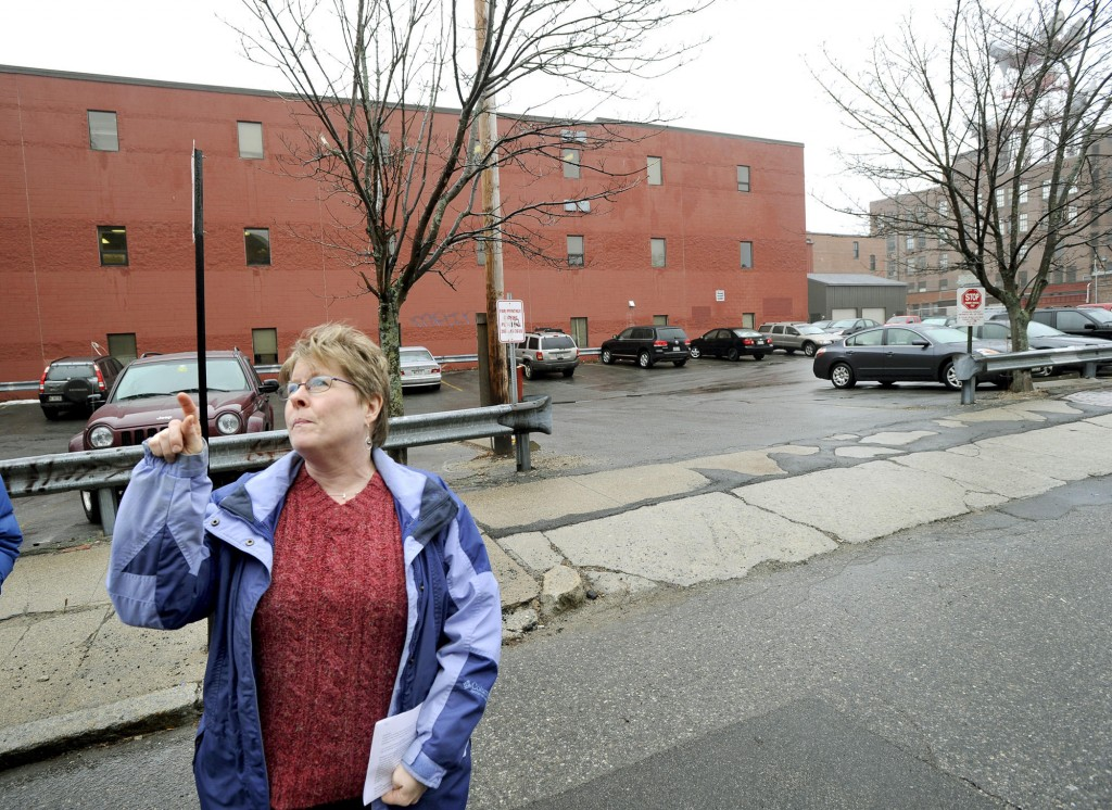"Susan Fitzpatrick points to her condo building while standing in front of an Oak Street parking lot where affordable housing is planned. Fitzpatrick opposes the project because ""I don't want my property's value driven down."""