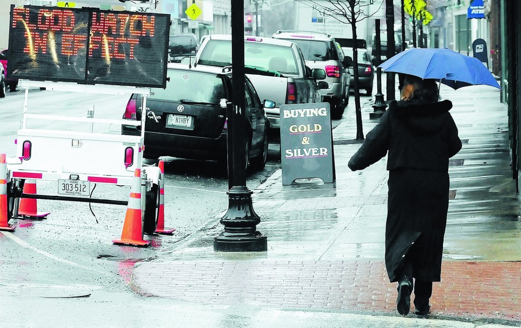 Staff photo by Joe Phelan A woman walks past a flood watch sign at the corner of Winthrop and Water Streets in downtown Augusta on a cold, rainy and windy Wednesday afternoon. A flood watch is in effect through Friday and the National Weather Service forecast calls for a rain snow mix.