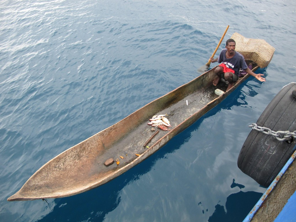 A fisherman from the Haitian port of Miragoane peddles his catch Saturday morning alongside the Sea Hunter. The ship's owner has been trying since Thursday to unload his cargo.