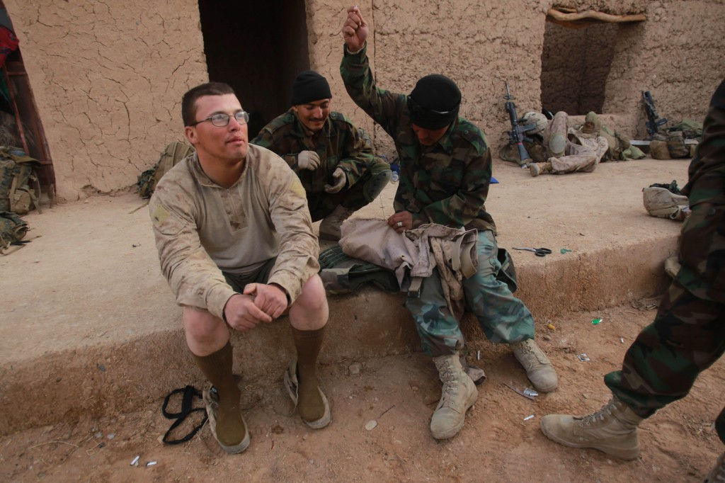 Marine Lance Cpl. William Smith has his torn pants mended by an Afghan National Army soldier in Marjah, Afghanistan, on Saturday.