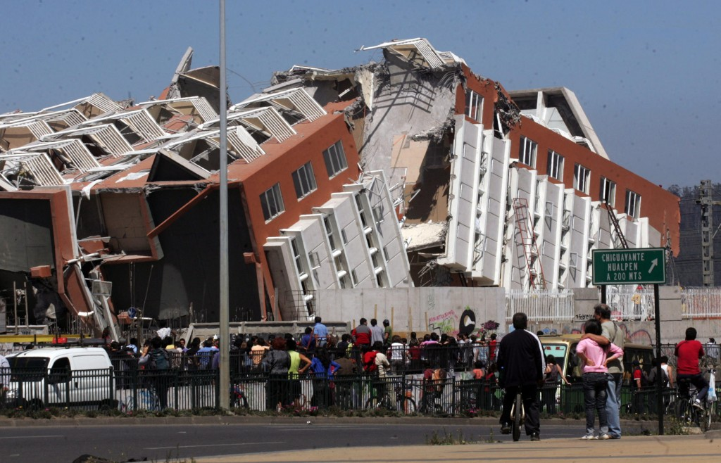 Residents look at a collapsed building in Concepcion, Chile, on Saturday after a magnitude-8.8 earthquake struck central Chile. The epicenter was 70 miles from Concepcion, Chile's second-largest city. The nation was rocked by more than 50 aftershocks topping magnitude-5, including one of magnitude-6.9.