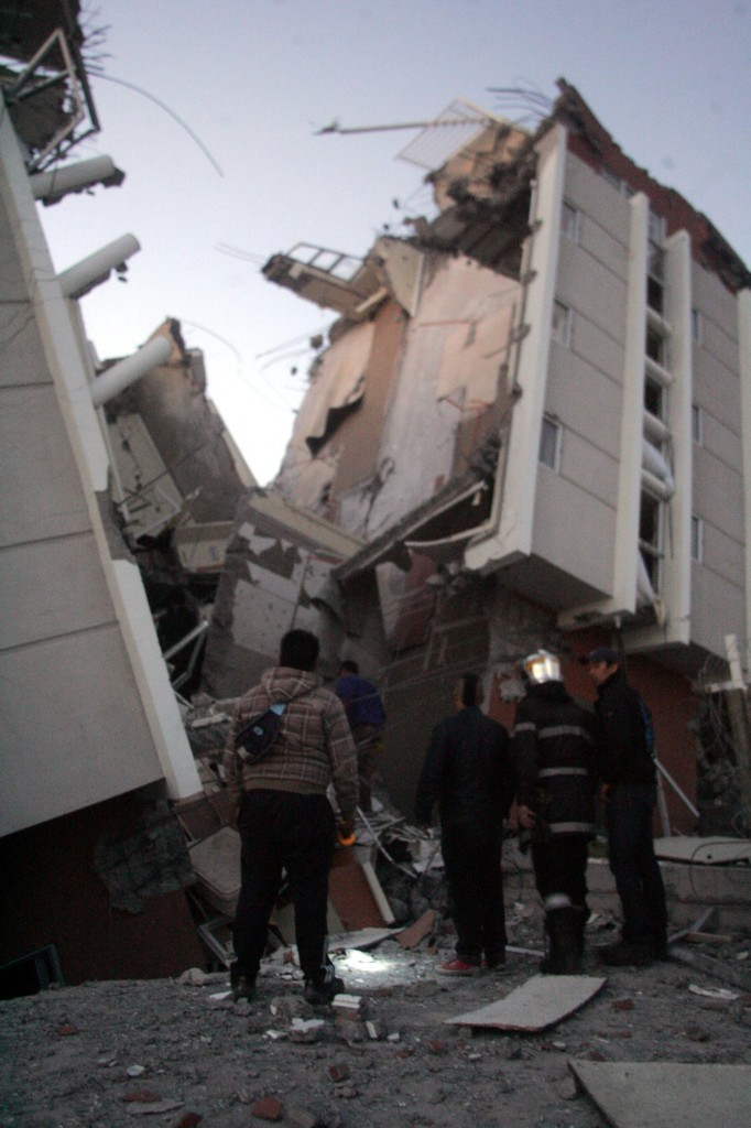 Residents look at a collapsed building in Concepcion, Chile, on Saturday after a magnitude 8.8 quake struck. The epicenter of the quake was 70 miles from Chile's second-largest city.