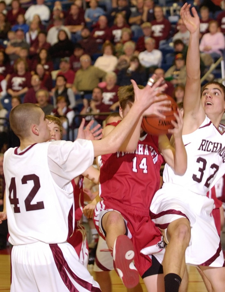 Stephen Osgood of Vinalhaven gets double-teamed by Thomas Carter, left, and Wade Tuttle.