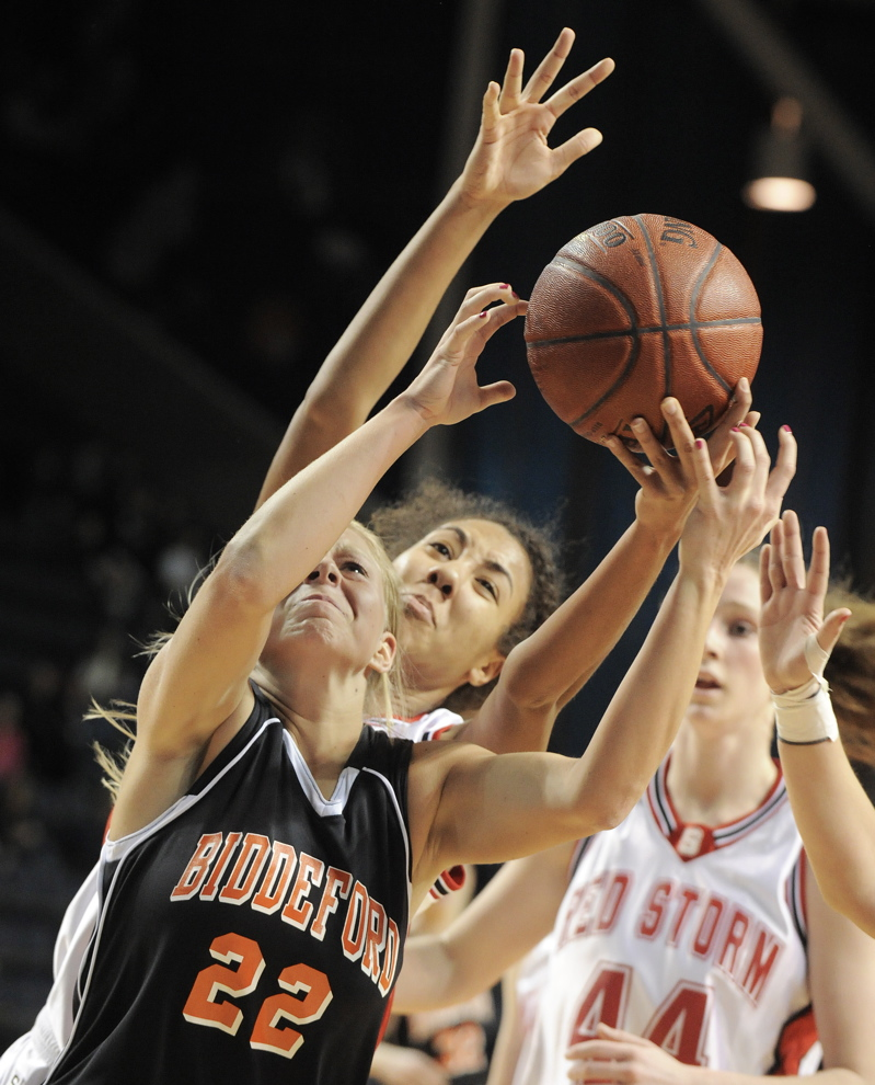Amethyst Hersom of Biddeford reaches for a rebound ahead of Carly Rogers of Scarborough during their Western Class A semifinal at the Cumberland County Civic Center. Scarborough will meet Deering in the final.