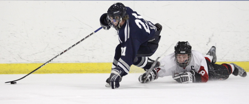Yarmouth's Alex Kurtz maintains control of the puck as he gets past Wayne Neiman of Camden Hills.