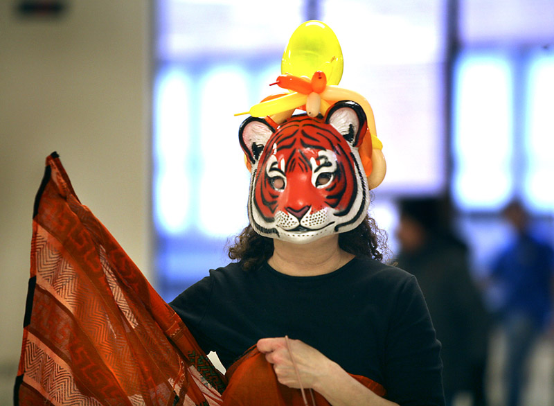Phyl Rubinstein of North Yarmouth, wearing a tiger mask, helps with the food.