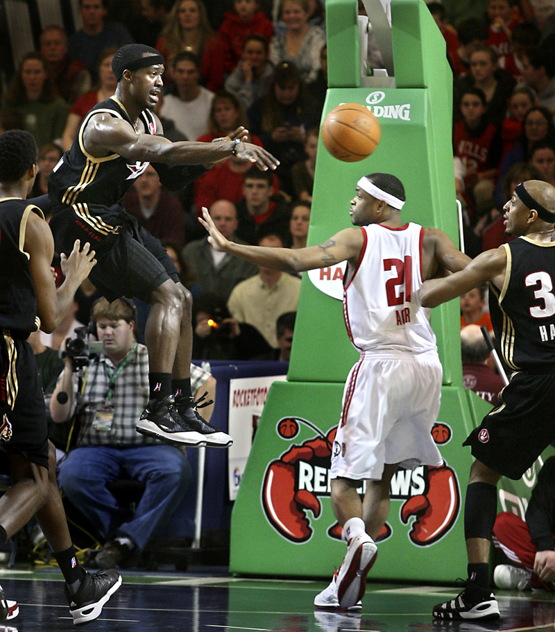 Maurice Ager of the Red Claws gets caught in the middle as Erie's Cedric Jackson flips a pass toward teammate Ivan Harris during Sunday's game at the Portland Expo. Portland held on for a 102-95 victory.