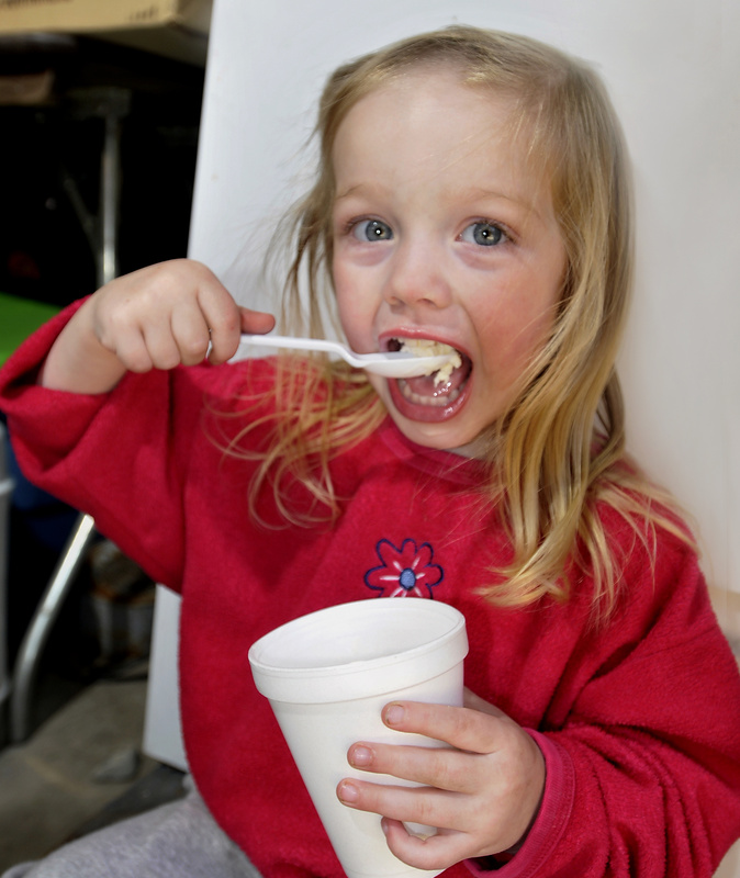Emma McKenney, 2, enjoys some vanilla ice cream with her family's homemade maple syrup at Grandpa Joe's Sugar House in East Baldwin.