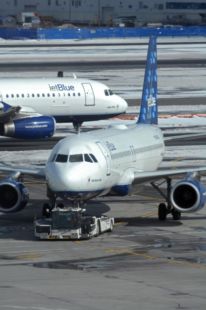 A JetBlue Airbus A320 taxis past another JetBlue plane being towed to a gate at John F. Kennedy International Airport in New York. The main runway at the airport will be closed for four months starting today.