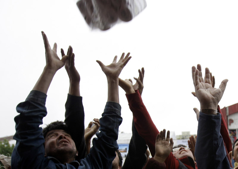 People reach for goods thrown from a supermarket window in Concepcion, Chile, today. Security forces said they arrested dozens of people for violating an anti-looting curfew.