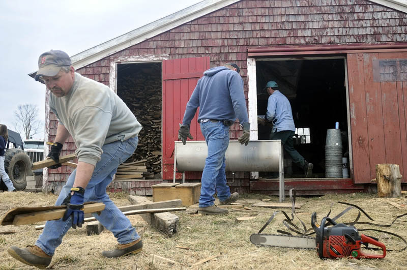 "PACKING UP: Jim Gilbert, left, collects slabs of firewood Sunday in front of Mark Fenderson's sugar shack in Whitefield. Several of Fenderson's friends helped him clean and pack up the shack after only making syrup for seven days this years. ""It was a pretty short season,"" Fenderson said."