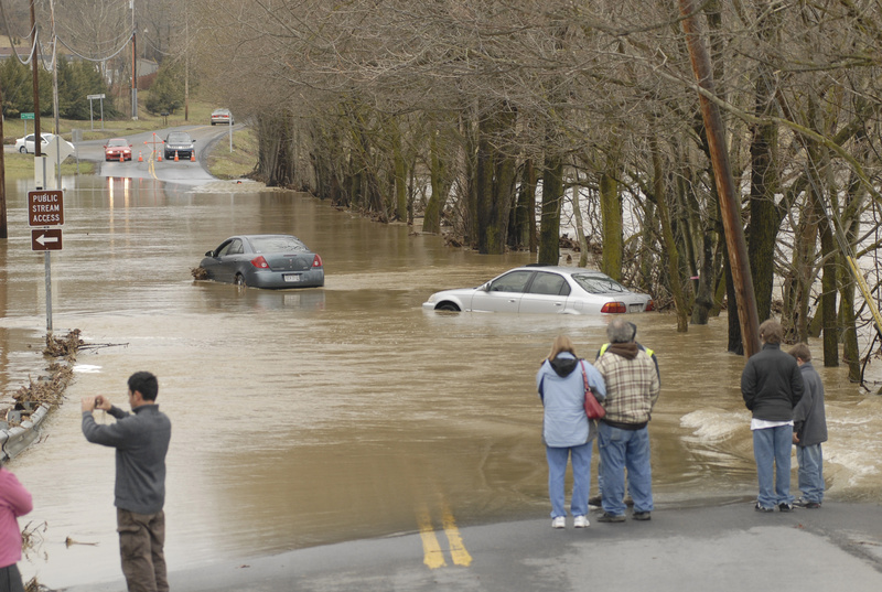 People stare at two abandoned vehicles that bogged down while the drivers were trying to cross Golf Course Road in Martinsburg, W.Va., Sunday. The Opequon Creek overflowed its banks Saturday, causing local officials to close several low-lying roads. In the Northeast, thousands lost power in Pennsylvania, New Jersey, New York and Connecticut. Flood