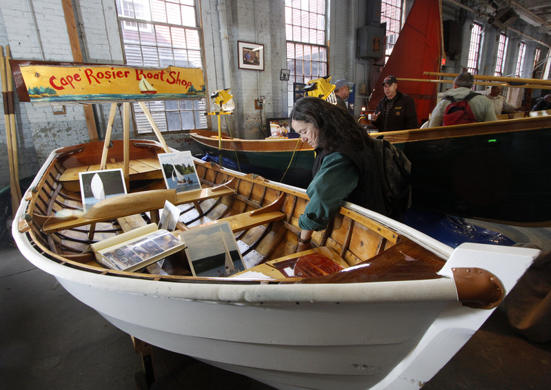 Suzanne Phillips of Cape Cod looks over a rowing and sailing dinghy made by Peter Chase of Cape Rosier Boat Shop in Harborside at the annual Maine Boatbuilders Show.