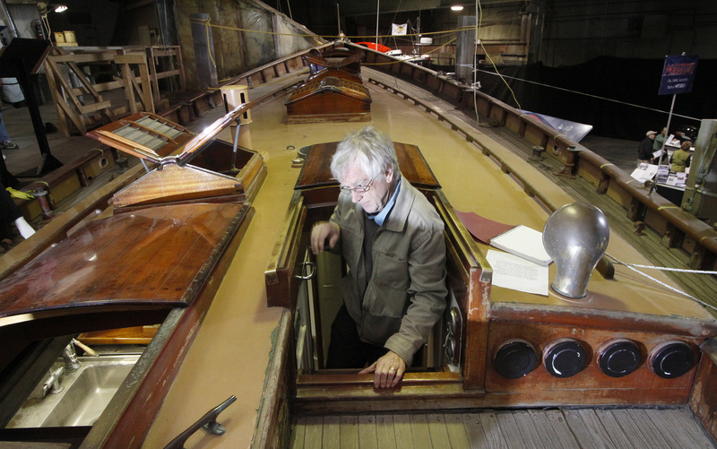 Jos Ruks of Portland climbs onto the deck of the Tar Baby, a 50-foot classic wooden yacht designed by John Alden and built by C.A. Morse & Son in Thomaston in 1929. He was among thousands of people who visited the Maine Boatbuilders Show, held Friday to Sunday. Below, Brian and Liz LaPoint of Rochester, N.H., stroll through the living quarters of the Alden Schooner Lion's Whelp, designed and built by Phineas Sprague.
