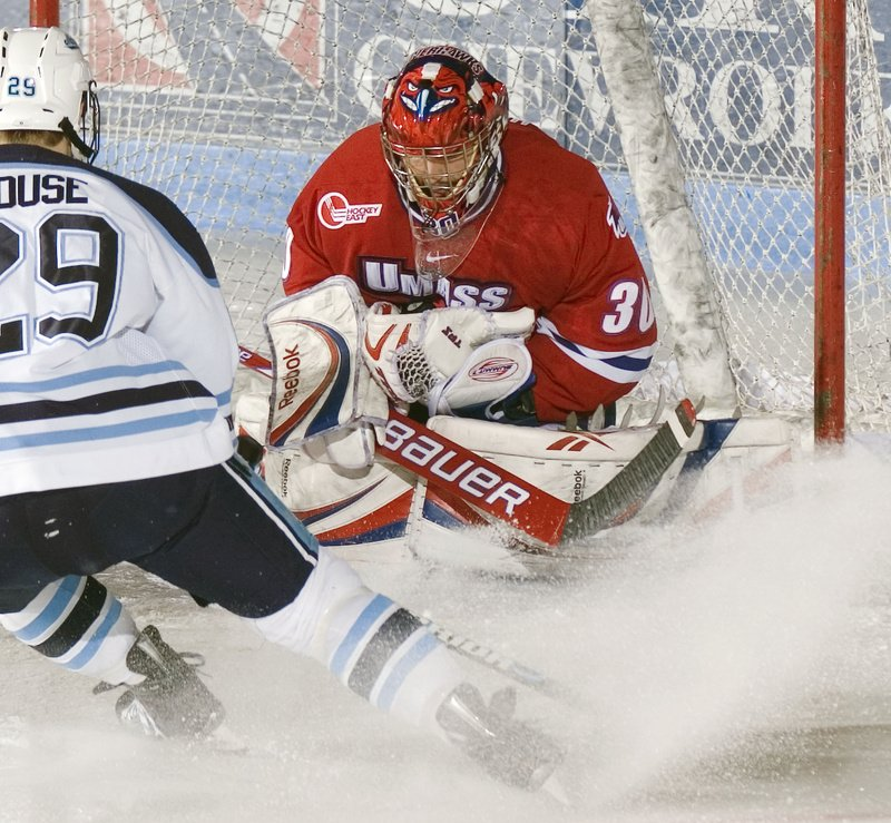 Lowell goalie Carter Hutton (30) cradles the puck in his glove after a shot by Maine's Tanner House (29) in the first period of an NCAA college hockey game Sunday, March 14, 2010, in Orono, Maine. (AP Photo/Michael C. York)
