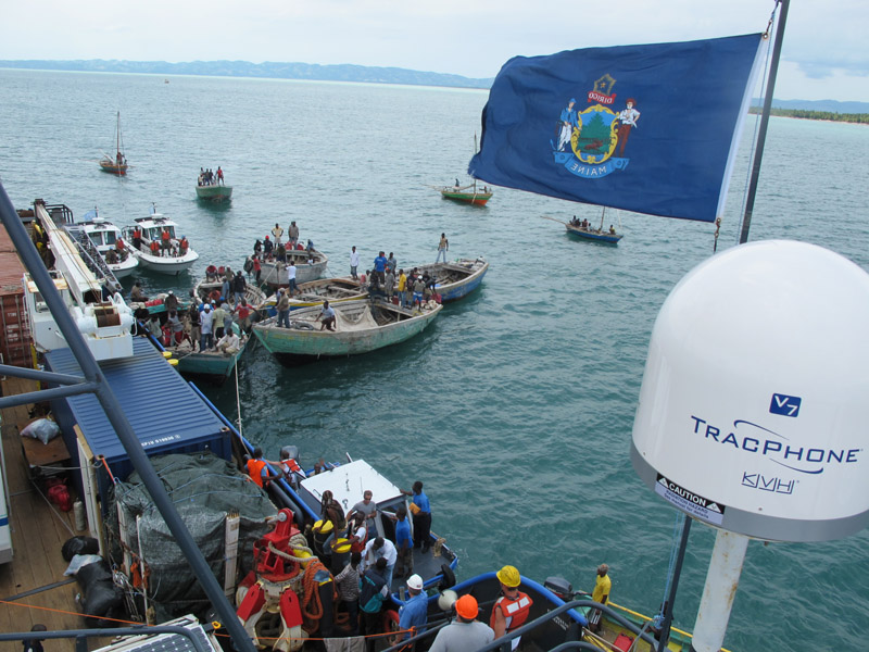 Haitian boats, monitored by two United Nations patrol boats, jockey for position alongside the Sea Hunter as offloading operations get under way today.